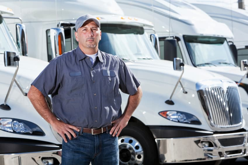 truck-driver-standing-in-front-of-big-rigs